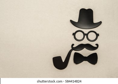 Happy fathers day sticker, hat, glasses, black mustache, tie bow and smoking pipe on paper background. Hipsters objects. father's day - holiday
