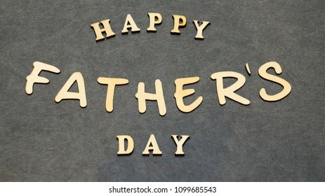 Happy father's day word combinations made of wooden letters on a black table. Father's day greetings.