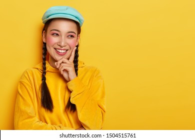 Happy feelings and emotions concept. Beautiful young woman with eastern appearance, touches rosy cheek with index finger, looks aside, has toothy smile, dressed in bright velvet hoody sweater