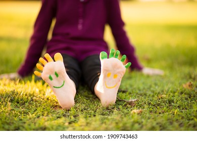 Happy feet with funny paint face outdoors in spring park. Child lying on green grass. Ecology concept