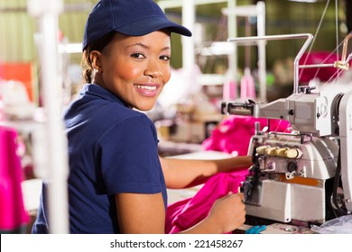 happy female african clothing factory worker sewing