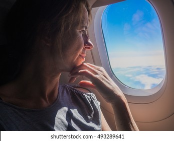 Happy, female airplane passenger enjoying the view from the cabin window over the blue sky
