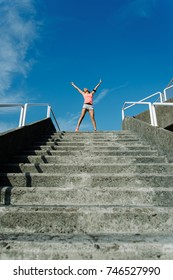 Happy female athlete raising arms to the sky for celebrating fitness or running workout goals and success.