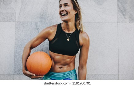 Happy female athlete standing against a wall after workout holding a basketball looking away.
