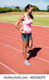 Happy female athlete warming up on the running track on a sunny day