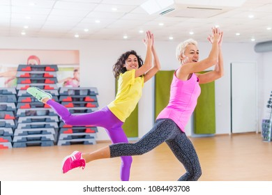 Happy female athletes doing aerobics exercises or Zumba dance workout to lose weight during group classes in fitness center