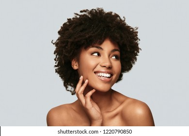 Happy female. Attractive young African woman looking away and smiling while standing against grey background