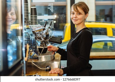 Happy female barista using the coffee machine durinf prepare cuppuccino at the cafe with window on background. Coffee business entrepreneur owner concept