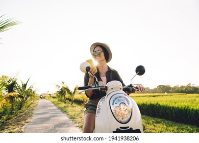 Happy female blogger in stylish sunglasses using mobile gadget for online networking resting at vintage moped, cheerful hipster girl holding modern cell device in hand sitting on retro scooter