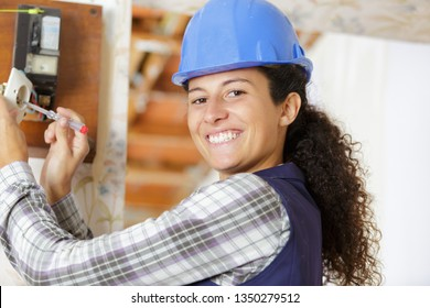 happy female builder with screwdriver fixing socket indoors