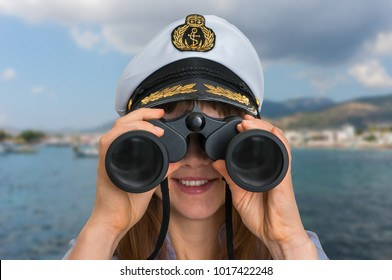 Happy female captain looks through a binoculars - marine concept