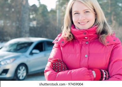 Happy female car owner standing in front of her automobile, smiling and looking at camera