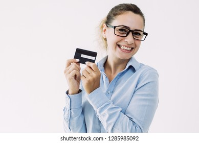 Happy female cardholder advertising loyalty program. Young Caucasian woman in office wear showing back of credit card. Money, transaction, paying concept