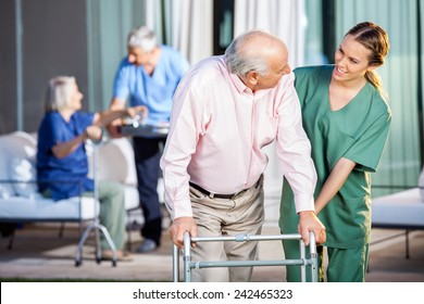 Happy female caretaker assisting senior man in using Zimmer frame at nursing home yard