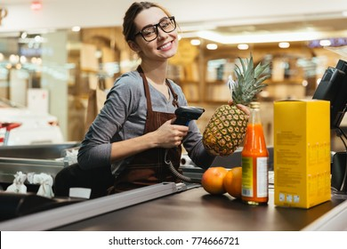 Happy female cashier scanning grocery items at supermarket