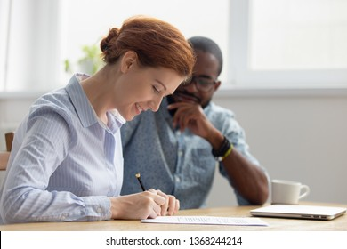 Happy female caucasian client customer hired employee signing contract meeting african american manager broker lawyer making insurance bank loan services commercial business deal write signature