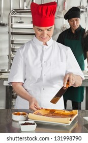 Happy female chef preparing chocolate roll in kitchen with colleague in background