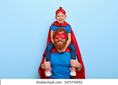 Happy female child sits on fathers shoulders, feels heroic and strong, wears red mask, cloak, play superhero, isolated on blue background. Lovely family have fantasy, pretend having supernatural power