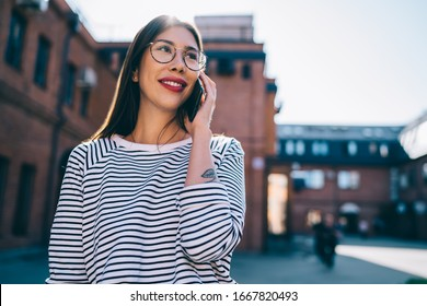 Happy female in classic glasses making positive international conversation via smartphone application during leisure time at urban setting, successful hipster girl in spectacles phoning via cellular