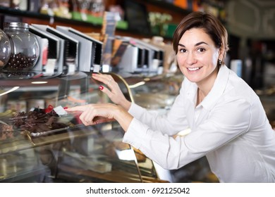 Happy female client choosing delicious dessert in confectionery