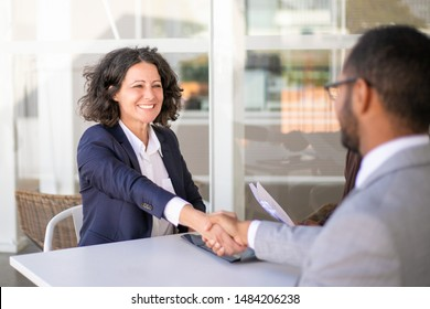 Happy female client thanking consultant for help. Business man and woman sitting at table, talking and shaking hands. Consulting concept