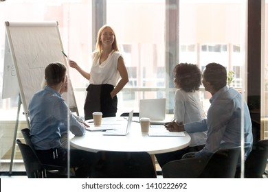 Happy female coach mentor leader presenting work results at business workshop in boardrooom behind closed glass door, smiling presenter speaker pointing on flipchart training workers sales board team