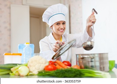 Happy female cook in toque works  at commercial kitchen