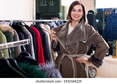 Happy female customer examining new sheepskin coat in women cloths store