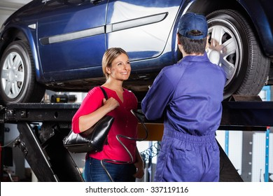 Happy female customer looking at mechanic refilling car tire at garage