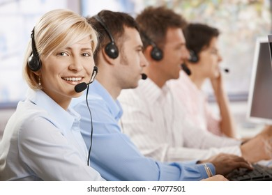 Happy female customer service operator recieving calls on headset, looking at camera, smiling.