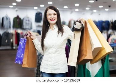 Happy female customer with shopping bags at clothing boutique