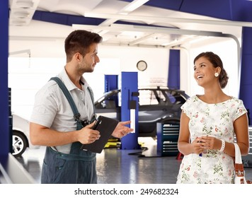 Happy female customer talking to car mechanic in auto repair shop, smiling happy.