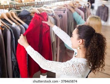 Happy female customers selecting coats and jackets at the shop