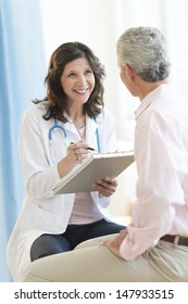 Happy female doctor with clipboard looking at patient in clinic