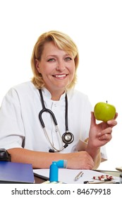 Happy female doctor at desk holding a green apple