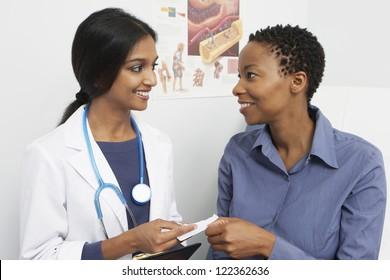 Happy female doctor giving prescription to patient