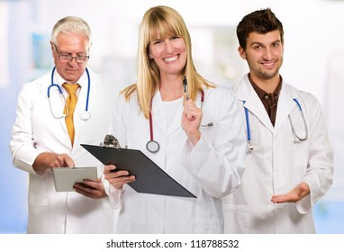 Happy Female Doctor Holding Clipboard In front Of Male Doctor, Indoors