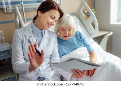 happy female doctor holding diagnosis and consulting senior woman lying in hospital bed