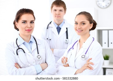 Happy female doctor with medical staff at the hospital. Successful team at health care concept