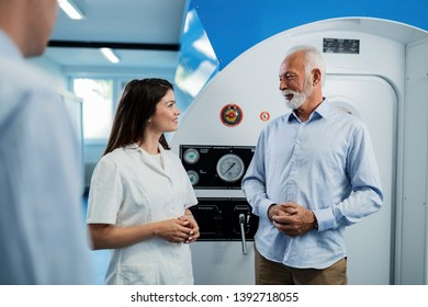 Happy female doctor and senior man communicating about therapeutic effects of hyperbaric chamber treatment.