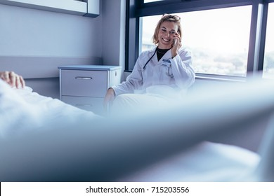 Happy female doctor sitting in hospital room and making a phone call. Medical professional in hospital ward using mobile phone.