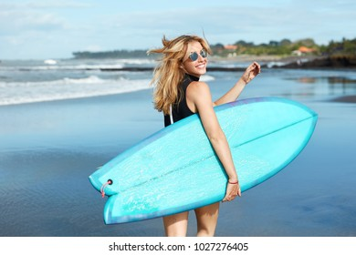 f11a0180 Happy female dressed in black swimsuit, wears trendy sunglasses, being in  good mood as