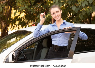 Happy female driver showing car key