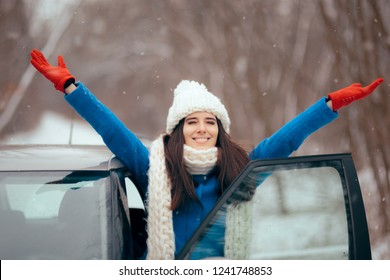 Happy Female Driver Standing By Her Car Admiring the Snow. Smiling girl next to her vehicle relaxing in winter journey trip