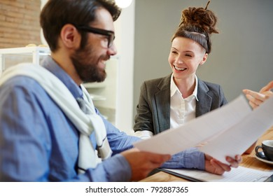 Happy female economist or banker and her colleague discussing papers or contracts