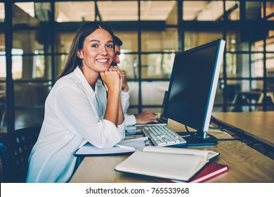 Happy female employee resting during work break looking at camera enjoying time in office, portrait of brunette cheerful woman satisfied with occupation collaborating with male colleague for project