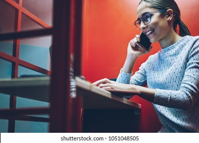 Happy female entrepreneur satisfied with productive business communication sitting in cabin with noise insulance, prosperous woman in eyewear excited with good news talking on telephone in box