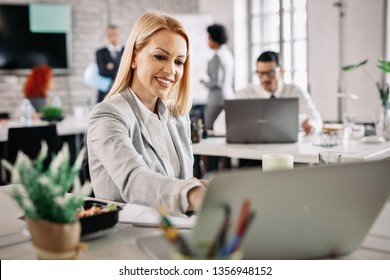Happy female entrepreneur using laptop while working at her office desk. There are people in the background.