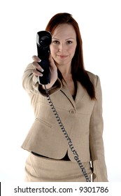 Happy female executive holding the phone receiver at arms length and smiling