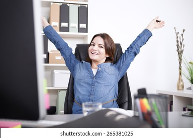 Happy Female Executive Sitting on her Chair at the Office While Stretching her Arms and Looking at the Camera.
